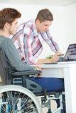 Jeune mâle sur le fauteuil roulant faisant le travail avec l'ami Photos stock