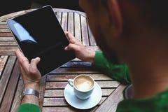 Jeune mâle utilisant le pavé tactile pour le travail à distance pendant le petit déjeuner de matin en café Photographie stock
