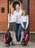 Jeune mère étreignant ses filles dans l'uniforme scolaire avant de laisser à l'école Images libres de droits