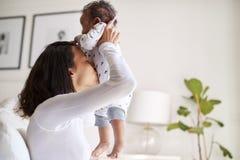 Jeune mère adulte d'Afro-américain heureux élevant son vieux fils de trois mois de bébé dans le ciel et embrassant son ventre, fi image libre de droits