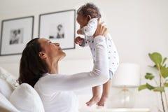 Jeune mère adulte d'Afro-américain heureux élevant son vieux fils de trois mois de bébé dans le ciel, souriant à lui, étroitement photos libres de droits