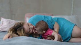 Jeune mère affectueuse embrassant son bébé banque de vidéos