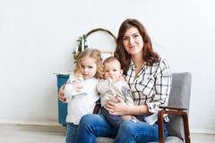 Jeune mère ainsi que petits deux enfants dans un intérieur de chambre Photos stock
