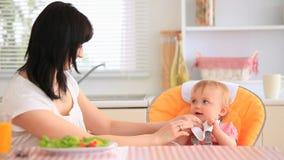 Jeune mère alimentant sa fille banque de vidéos