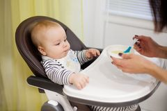 Jeune mère alimentant son petit fils de bébé avec le gruau, qui se reposant dans la haute chaise de bébé pour l'alimentation Images libres de droits