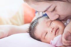 Jeune mère asiatique embrassant son bébé nouveau-né avec amour Images libres de droits