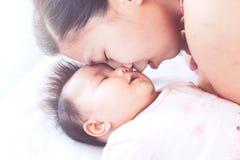 Jeune mère asiatique heureuse embrassant son bébé nouveau-né avec amour Images stock