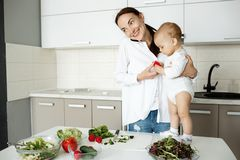 Jeune mère attirante avec les cheveux foncés faisant cuire le dîner et parlant au téléphone avec le mari tandis que petit fils se Image stock
