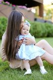 Jeune mère avec de longs cheveux se reposant sur l'herbe avec peu de fille images stock