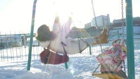 Jeune mère avec l'enfant balançant sur extérieur réglé d'oscillation en parc d'hiver Neige tombant, chutes de neige, horaire d'hi