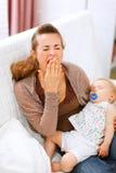 Jeune mère avec la chéri de sommeil sur des embardées de mains Photo libre de droits