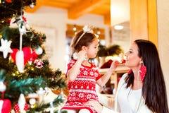 Jeune mère avec la fille à l'arbre de Noël à la maison Photographie stock libre de droits