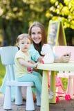 Jeune mère avec la fille s'asseyant dans la chaise de bébé en parc Photo stock
