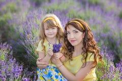 Jeune mère avec la jeune fille souriant sur le champ de la lavande Fille s'asseyant sur des mains de mère Fille dans coloré Photos stock