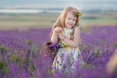 Jeune mère avec la jeune fille souriant sur le champ de la lavande Fille s'asseyant sur des mains de mère Fille dans coloré Image stock