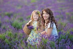 Jeune mère avec la jeune fille souriant sur le champ de la lavande Fille s'asseyant sur des mains de mère Fille dans coloré Photographie stock