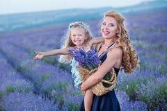 Jeune mère avec la jeune fille souriant sur le champ de la lavande Fille s'asseyant sur des mains de mère Fille dans coloré Photographie stock libre de droits