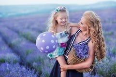 Jeune mère avec la jeune fille souriant sur le champ de la lavande Fille s'asseyant sur des mains de mère Fille dans coloré Images libres de droits