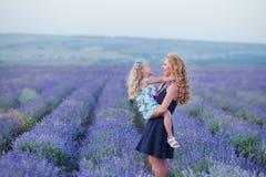 Jeune mère avec la jeune fille souriant sur le champ de la lavande Fille s'asseyant sur des mains de mère Fille dans coloré Images stock