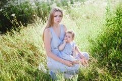 Jeune mère avec la petite fille sur la nature Photographie stock libre de droits