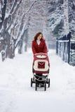 Jeune mère avec la voiture d'enfant Images libres de droits