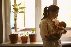Jeune mère avec le bébé à la maison photographie stock
