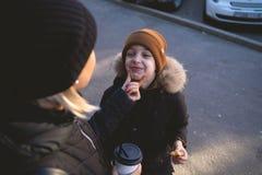 Jeune mère avec le fils manger de la nourriture de rue à l'horaire d'hiver et avoir un amusement image stock