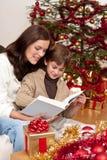 Jeune mère avec le livre de relevé de fils sur Noël Image libre de droits