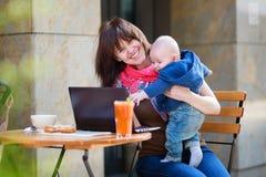 Jeune mère avec le petit fils travaillant sur son ordinateur portable photo libre de droits