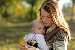 Jeune mère avec sa chéri dans un transporteur image libre de droits