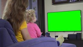 Jeune mère avec sa montre TV de fille d'enfant et doigt d'exposition Écran vert de chroma clips vidéos