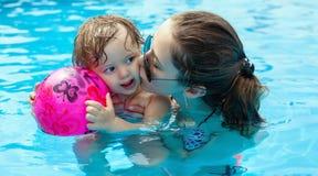 Jeune mère avec sa petite fille dans la piscine photos stock