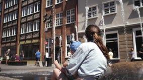 Jeune mère avec ses petits regards de fils à la fontaine banque de vidéos