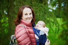 Jeune mère avec son bébé dans le transporteur marchant ensemble en parc Photo libre de droits
