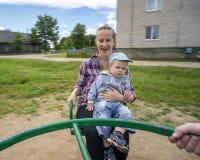 Jeune mère avec son fils 1 3 ans montant sur le carrousel Photographie stock