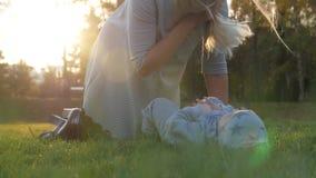 Jeune mère avec son petit bébé jouant en parc d'automne sur le coucher du soleil Le bébé se trouve sur l'herbe Famille heureux clips vidéos