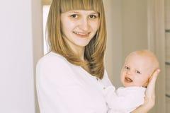 Jeune mère avec un enfant bébé en main dans son objection de visage Photos libres de droits