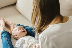Jeune mère avec un petit bébé sur le divan Ils sont heureux Images libres de droits