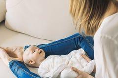 Jeune mère avec un petit bébé sur le divan Ils sont heureux Photo stock