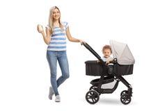 Jeune mère avec une bouteille de lait et d'un bébé garçon dans une poussette image libre de droits