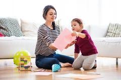 Jeune mère avec une petite fille à la maison, dessinant Photographie stock