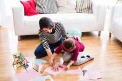 Jeune mère avec une petite fille à la maison, dessinant Photo libre de droits