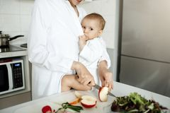 Jeune mère belle allaitant son fils mignon nouveau-né sur la table de cuisine tout en faisant cuire le petit déjeuner sain pour l Image libre de droits