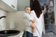 Jeune mère belle avec les cheveux foncés tenant le fils nouveau-né sur des mains et recherchant l'aliment pour bébé dans le réfri images stock