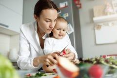 Jeune mère belle sérieuse passant le temps avec son fils nouveau-né faisant cuire le dîner et montrant comment couper des légumes Photographie stock libre de droits