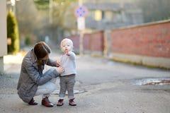 Jeune mère boutonnant son chemisier de childs Image stock