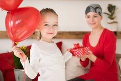 Jeune mère, cancéreux, et sa fille mignonne, célébrant la maison de retour de l'hôpital Maison ou fête d'anniversaire bienvenue Photo stock
