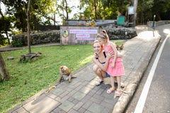 Jeune mère caucasienne avec la fille tenant les singes proches au zoo en Thaïlande images libres de droits