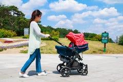 Jeune mère coréenne poussant la poussette photographie stock libre de droits