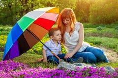 Jeune mère détendant avec son petit fils dans le jardin Concept de jour du ` s de mère Photo libre de droits